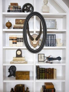 Balanced Bookshelf: Notice your eye travels from the top left and zig zags toward the bottom. This is an excellent use of larger items in a dark color    against lighter items. Anchored with an open frame and skull mounted on the outside of the shelf.